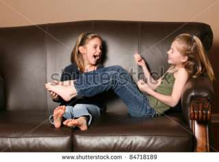 Cute Little Girl Tickling SisterS Feet Stock Photo 84718189
